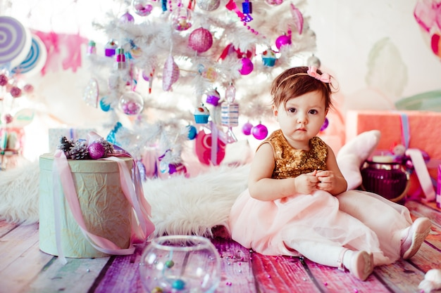 Girl in golden dress sits among present boxes before christmas tree