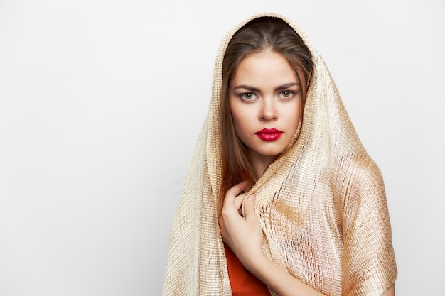A girl in a golden scarf covers the head of the studio charm elegant style close-up