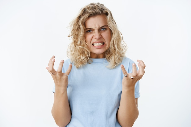 Girl gonna blow out over anger and distress clench teeth and fists in fury and dismay frowning being pressured and distressed full of hate, looking angry at camera over white wall