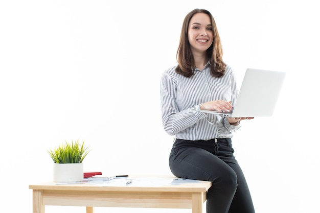 A girl in a good mood is sitting on a table and typing on a computer on a white background
