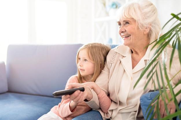 Girl and grandma watching tv