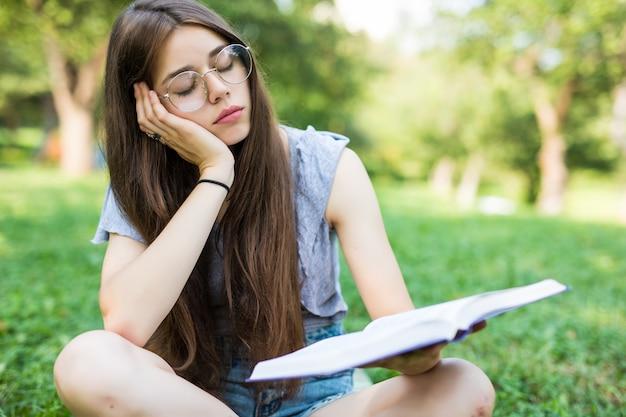 Ragazza sull'erba sulla coperta sensazione di stanchezza durante il tentativo e annoiato leggere il libro per rilassarsi fuori con i libri