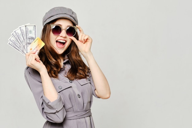 Girl in a gray dress and glasses holds us dollars and a credit bank card. copy space.