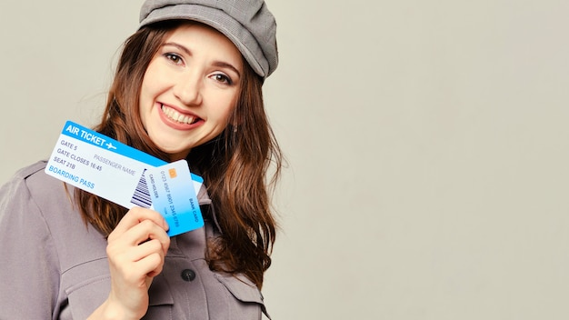 A girl in a gray dress looks at the camera and holds plane tickets with a credit card. copy space.