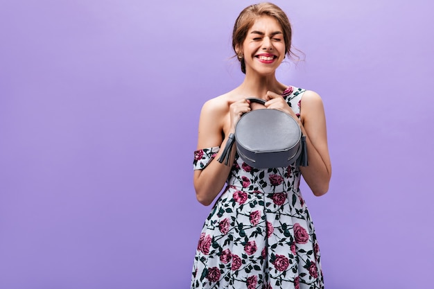 Girl in great mood holds grey handbag. happy charming young woman in floral print dress posing with small trendy bag on isolated backdrop.