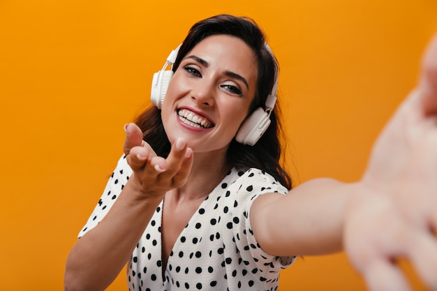 Girl in great mood is listening to music with headphones and taking selfie on orange background