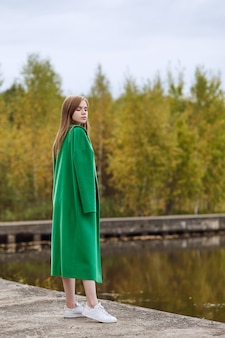 Girl in a green coat walks along the lake embankment on a cloudy autumn day. autumn fashion and clothing, yellow fallen leaves floating in the water. romantic mood