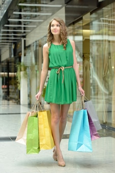 The girl in the green dress carries bags.