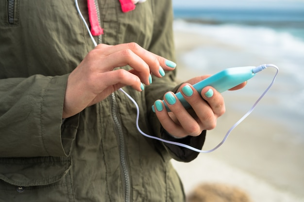 Girl in a green jacket, listening to music with headphones on the phone and walking on the beach
