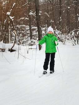 Girl in a green jacket skiing in the winter sunny forest.