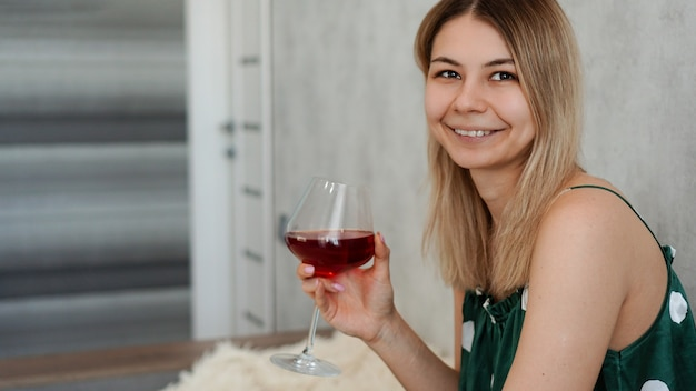 Girl in green pajamas in bed with a glass of red wine. morning wine in bed
