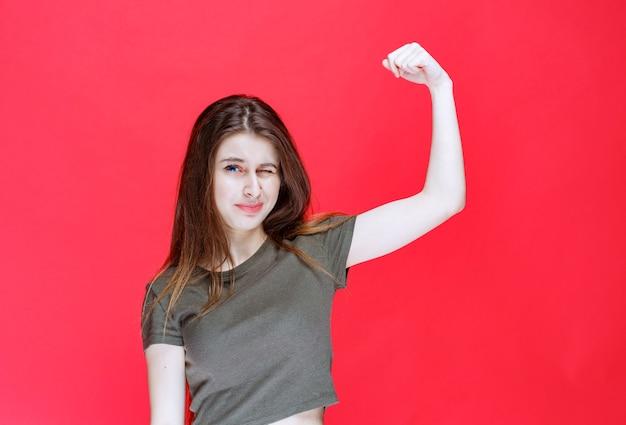 Ragazza in camicia verde che dimostra i suoi muscoli del braccio.