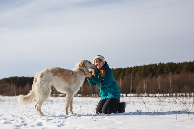 A girl in a green ski jacket on her knees and a russian white hound