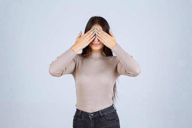 Ragazza in camicia grigia chiudendo il viso con la mano.