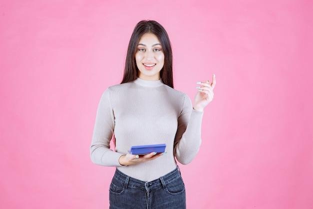 Ragazza in camicia grigia che tiene una calcolatrice blu e che sorride con fiducia