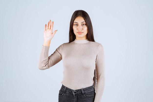 Ragazza in camicia grigia alzando le mani.