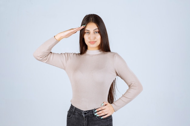 Girl in grey shirt saluting like a soldier.