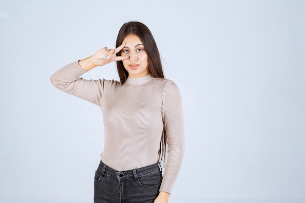 Girl in grey sweater doing peace hand sign.