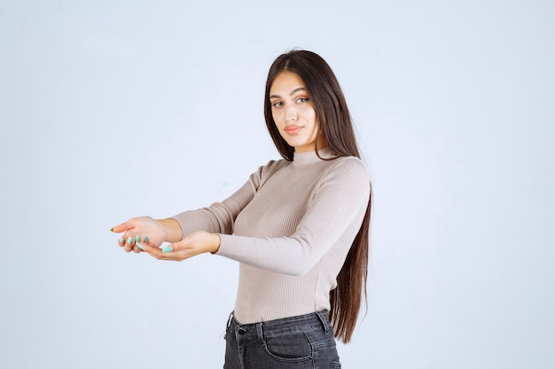 Girl in grey sweater opening her hands.