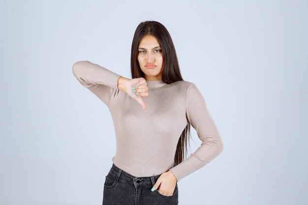 Girl in grey sweater pointing down.