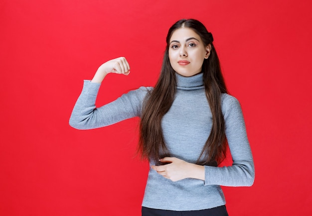Girl in grey sweater showing her arm muscles.