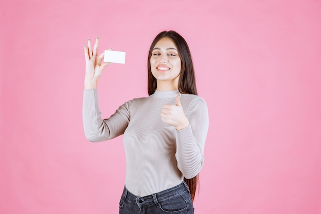 Girl in grey sweater showing her new business card making good hand sign