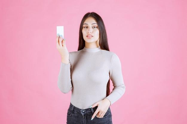Ragazza in maglione grigio, mostrando e presentando il suo biglietto da visita