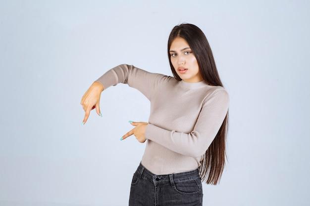 Ragazza in maglione grigio che mostra qualcosa a sinistra.