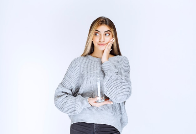 Girl in grey sweatshirt holding a glass of pure water and making doubting face.