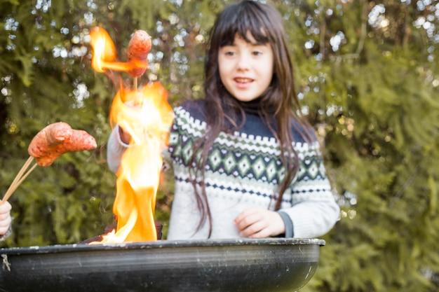Ragazza grigliare salsiccia nel fuoco sul barbecue portatile