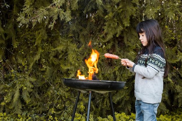 야외 바베 큐에 소시지를 굽고 소녀