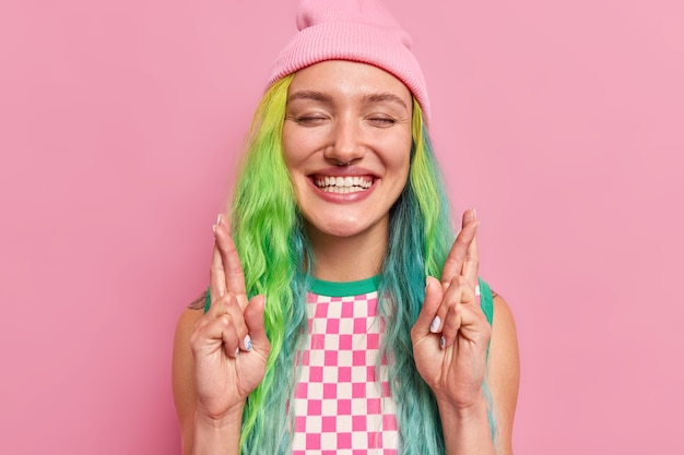 Girl grins happily at camera crosses finger for wish come true keeps eyes closed feels thrilled to see happy outcome wears hat checkered dress isolated on pink