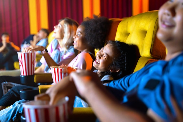 The girl and group of kid are seating and watching at movie theater.