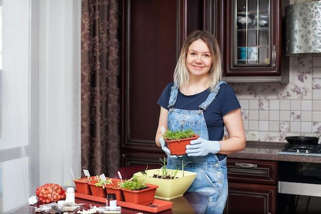 소녀는 집의 부엌에서 야채와 허브의 모종을 자랍니다.