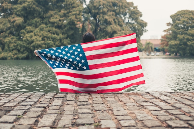 Girl guarding the us flag with a background lake.