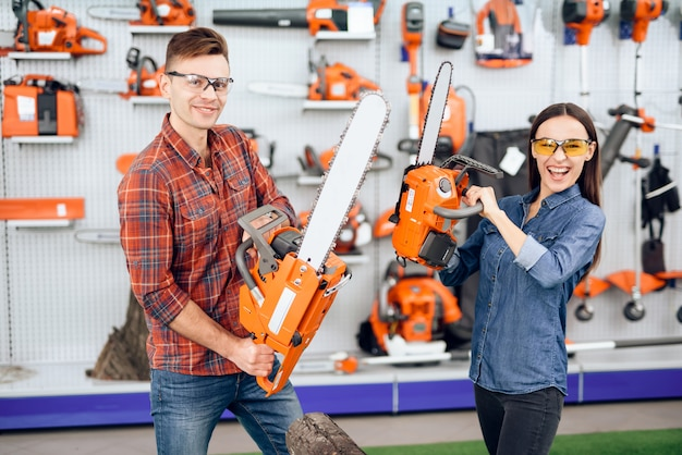 The girl and the guy check how the chainsaw works.