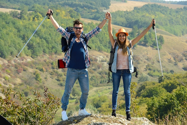 Girl and guy climbed mountain and raised their hands up.