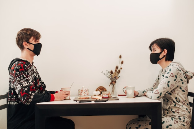 Girl and guy drinking tea at home in masks.