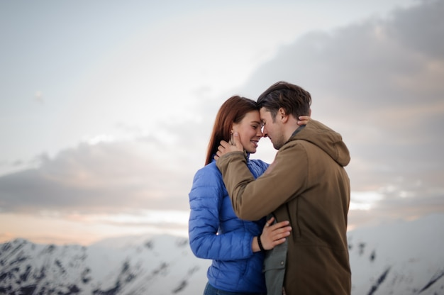 Girl and a guy gently embrace each other on the scene of snow mountains