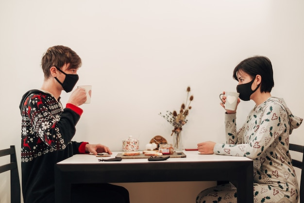 Girl and guy have breakfast at home in masks.