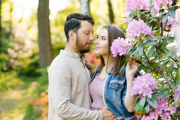 Girl and guy, in love with each other, happy to be together. they smile and walk in the flowering gardens of rhododendron