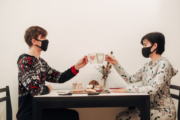 Girl and guy on quarantine drinking coffee in masks.