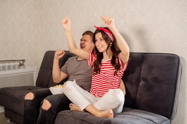 Girl and guy watching tv at home and eating popcorn