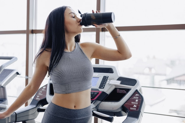 Girl in the gym are trained on treadmill and drink water
