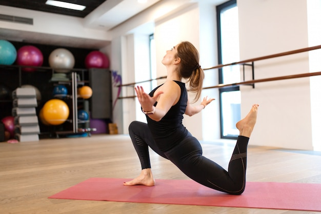 The girl in the gym does yoga to keep herself in shape or control excess weight.