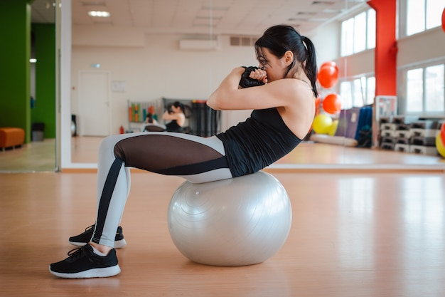 Girl in the gym doing fitness exercises.