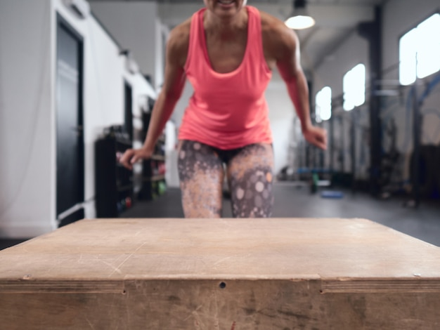 Girl in a gymnasium about to jump over a box