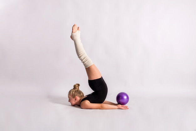 A girl gymnast in a black swimsuit performs a gymnastic exercise with a ball on a white isolated wall with space for text