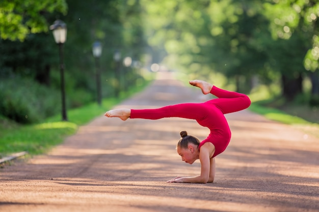 Girl gymnast in a bright red overalls doing an exercise on the track in the park on a warm sunny summer evening