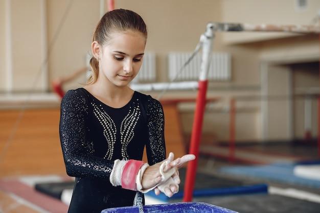Ginnasta ragazza in impugnature di ginnastica spalmando il gesso della palestra bambino in una scuola di atletica leggera.